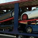 An open car transporter carrying prestige cars
